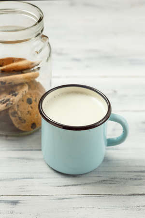Chocolate chips cookies and a glass of milk on a white wooden background Stock Photo