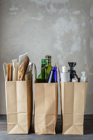 Three paper bags with sorted household waste: paper, glass and plastic. Grey concrete background with copy space. Recycling and ecology concept.