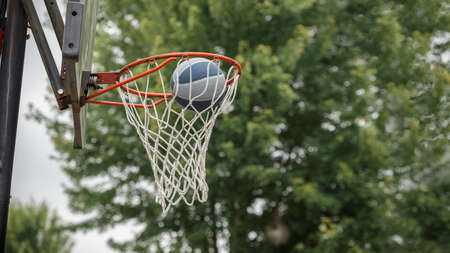 Ball is falling into the basketball hoop in the park