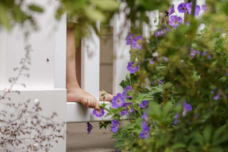 Boys bare feet on the porch fence in the front of a house among flowers and bushes in the garden