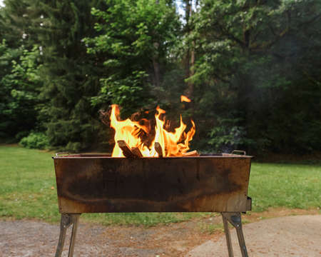 Public outdoor charcoal grill in the summer park with wood ashes and fire flames preparing for grilling.