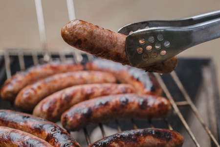 Grilling sausages on barbecue grill outdoor. Picnick in the park or forest. Selective focus