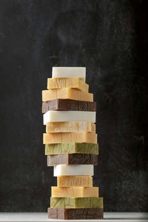 Tower stack of different kinds of handmade solid soap bars and shampoo over grey background