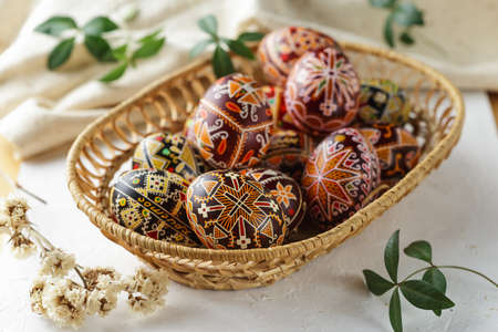 Big woven dish with Pysanky. Ukrainian Easter eggs decorated with wax-resist dyeing technique, traditional for Eastern European countries