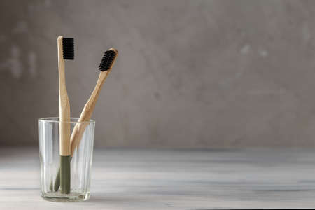 Two eco friendly bamboo tooth brushes in a glass. Zero Waste concept. Copy space for text Stock Photo