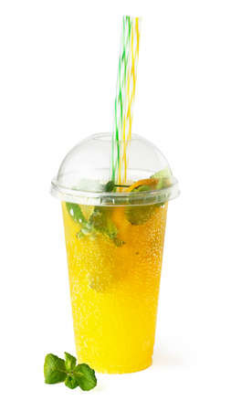 Cooling orange lemonade drink in plastic glass with mint and sparkling water isolated on white background