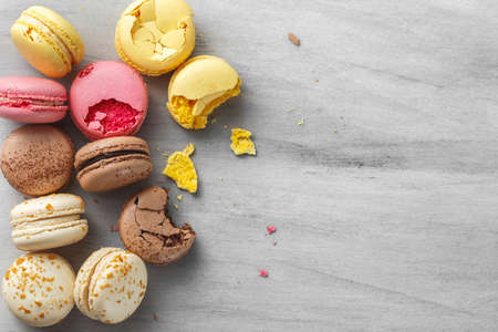 French macarons scattered over grey wooden background, top view Stock Photo