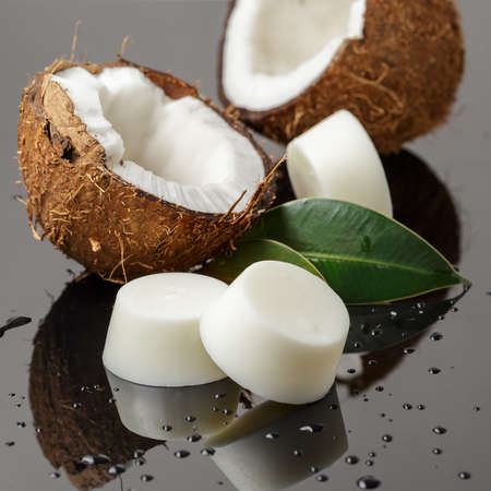 Handmade solid soap or shampoo or conditioner bars and fresh coconuts on reflective surface