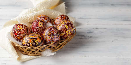 Pysanky, Ukrainian Easter eggs decorated with wax-resist dyeing technique, white wooden background, copy space for text