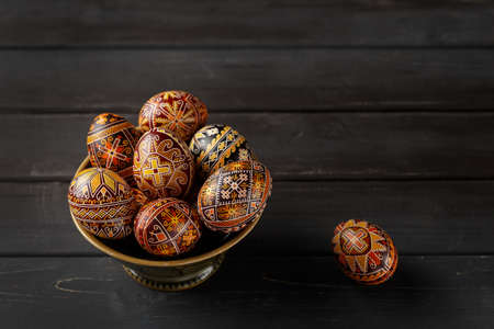 Pysanky in a bowl, Ukrainian Easter eggs decorated with wax-resist dyeing technique, black wooden background