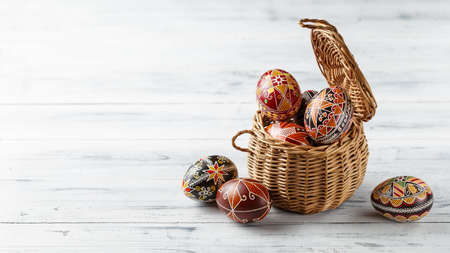 Pysanky in the basket, Ukrainian Easter eggs decorated with wax-resist dyeing technique, white wooden background, copy space for text