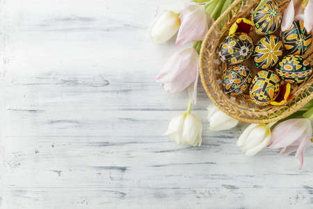 Pysanky, Ukrainian Easter eggs decorated with wax-resist dyeing technique, tulip flowers on white wooden background, copy space for text