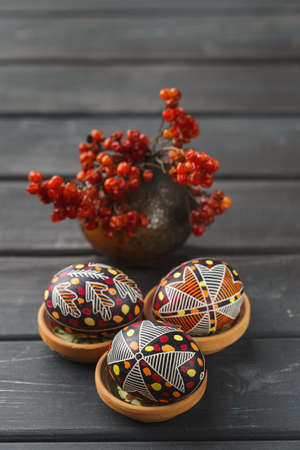 Pysanky, Ukrainian Easter eggs decorated with wax-resist dyeing technique, guelder rose on black wooden background Stock Photo - 134713129