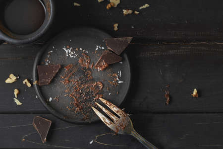 Black empty plate with cake leftovers from above on wooden background