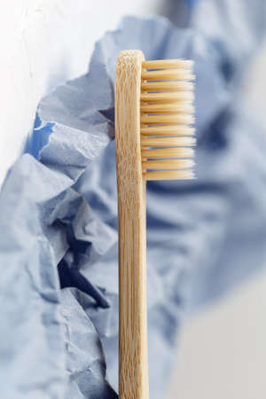 Close up of bamboo toothbrush on a white and purple paper background. Eco friendly products, zero waste concept