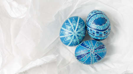 Pysanky on the white crumpled paper background. Easter eggs decorated with wax-resist dyeing technique, traditional for Eastern European countries, wide format, top view, copy space