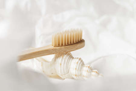 Close up of bamboo toothbrush on a seashell over white crumpled paper background. Eco friendly products, zero waste concept
