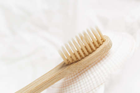 Close up of bamboo toothbrush on a seashell over white crumpled paper background. Eco friendly products, zero waste concept Stock Photo - 134713225