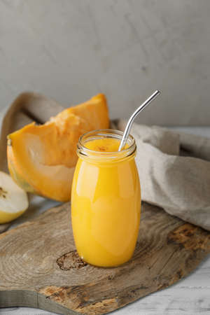 Traditional autumn pumpkin smoothie with apple and cinnamon in glass jar on neutral grey background