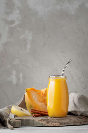 Traditional autumn pumpkin smoothie with apple and cinnamon in glass jar on neutral grey background. Copy space for your text