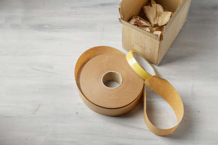 Packaging paper tape, narrow cellulose adhensive tape and brown paper box. Alternative plastic free packaging stuff for sustainable shipping and delivery service Standard-Bild