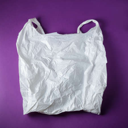 Square photo of the White Wrinkled Plastic Bag On Purple Background Stock Photo