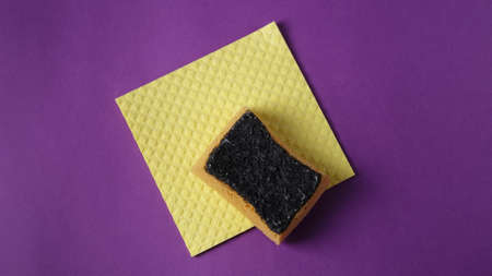 Cleaning equipment on a vivid purple background: yellow sponge for washing dishes, cleaning wipe, the concept of plastic cleaning tools, top view