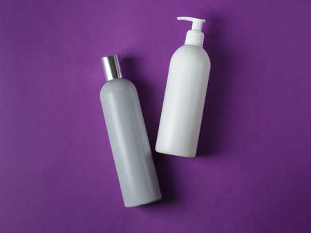 Blank grey shampoo and white conditioner cosmetic bottles on vivid purple background