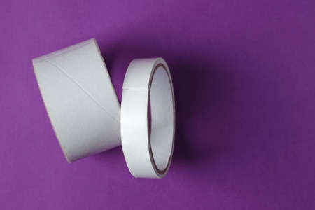 Two rolls of sticky adhesive scotch tape on purple background