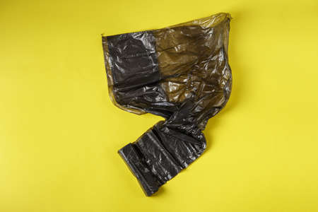 Black roll of plastic garbage bags on yellow background