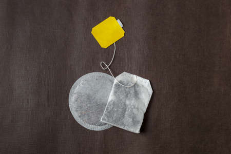 Teabags with yellow label. Top view, on a dark brown background. Mockup