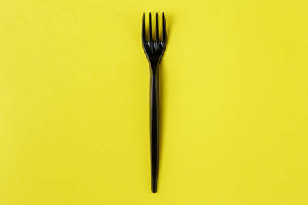 Black plastic fork on yellow background. plastic pollution