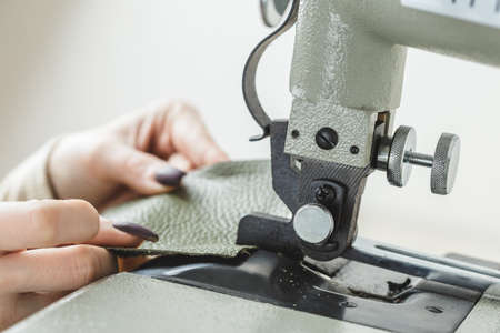 Young white woman stitching leather using a sewing machine