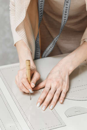 Leather craftswoman working making measuremets in patterns at table in workshop studio. Small business and mastership concept