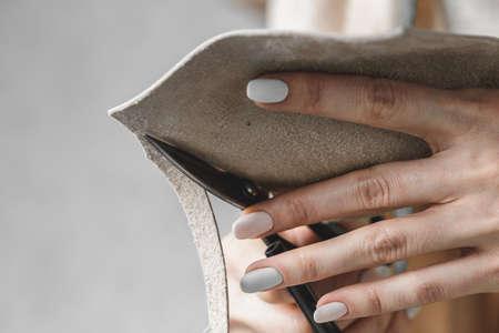 Female handbag designer measuring leather and cutting out details in a workshop studio