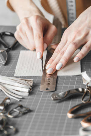 Female handbag designer measuring and cutting leather in a workshop Stock Photo