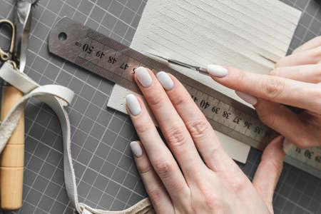 Female craftswoman measuring and cutting white leather fringe for boho style handbag details Stock Photo