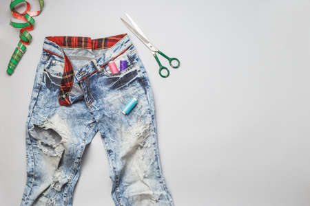 Old raped jeans with holes and sewing tools top view