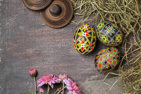 Pysanky, Ukrainian Easter eggs decorated with wax-resist dyeing technique, hay and flowers on wooden background Stock fotó