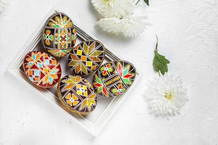 Pysanky, Ukrainian Easter eggs decorated with wax-resist dyeing technique on white wooden background Archivio Fotografico