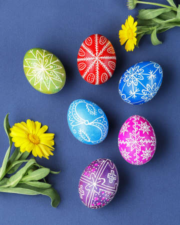 Pysanky, Ukrainian Easter eggs decorated with wax-resist dyeing technique, flowers on blue background