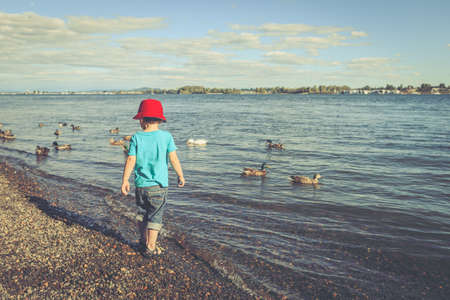 Little boy on the river beach in the afternoon. Kid is wearing blue t-shirt, denim shorts and red hat. Summer activities concept 版權商用圖片