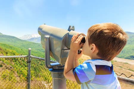 Little boy using telescope to see Mount St. Helens peak from observation point, Washington state, USA
