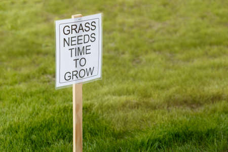 Grass Needs Time To Grow Sign requesting others to stay off the freshly planted grass