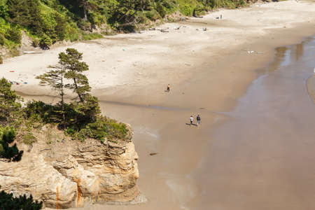 High angle view on Sandy Beach with few people walking at Pacific Ocean Coastline, Oregon, USA