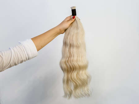 Famale hand holding a bundle of blonde natural remy human hair extensions over white background Banque d'images