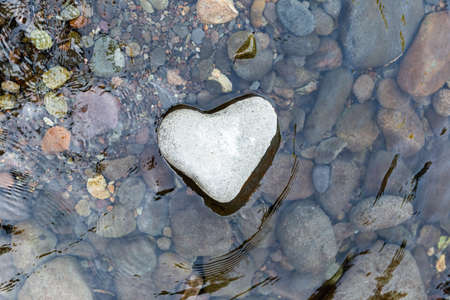 Beautiful heart shaped stone in the river water. Valentine's Day celebration background