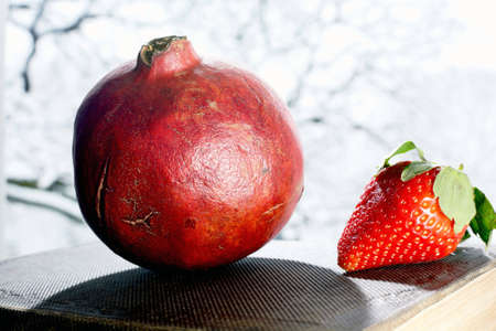 Pomegranate and strawberry on the book.