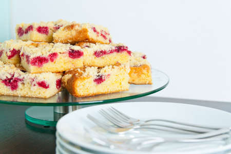 Raspberry Streusel Cake sliced on a table with dishes and coffee cups