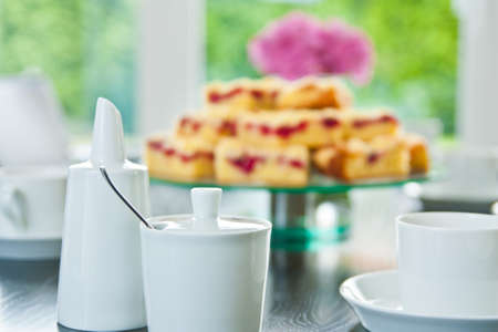 inddor: Raspberry Streusel Cake sliced on a table with dishes and coffee cups